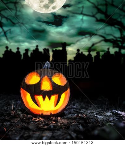 Scary halloween pumpkin with graveyard background. Empty space for text