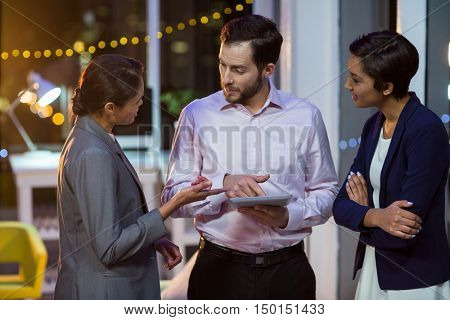 Businesspeople interacting with each other while using digital tablet in office at night