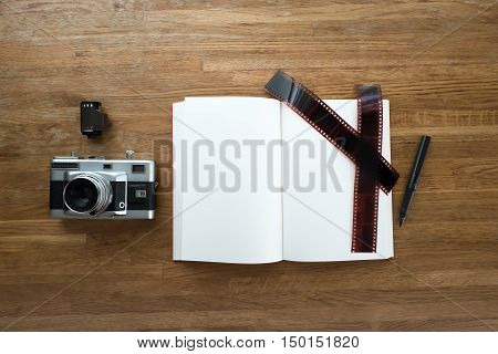 35mm film camera notebook pen film strip and film roll lay on wooden table view from top with CopySpace