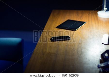 Digital tablet and mobile phone on office desk at night