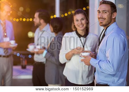Businesspeople having coffee during break in office at night