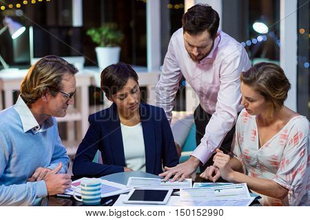 Businesspeople discussing on documents in office at night