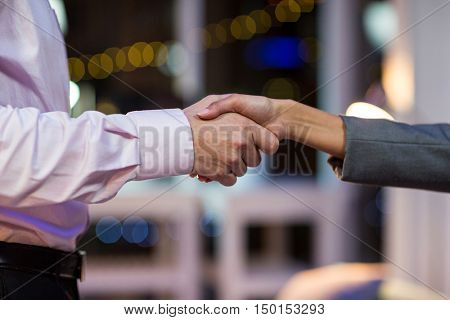 Close-up of businesspeople shaking hands in office at night