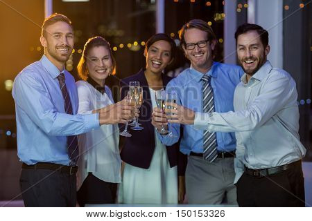 Portrait of businesspeople toasting glasses of champagne in office at night