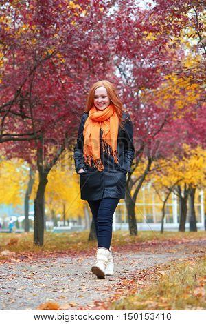 girl walk on pathway in city park with red trees, fall season