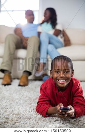 Boy holding remote while lying on the floor at home