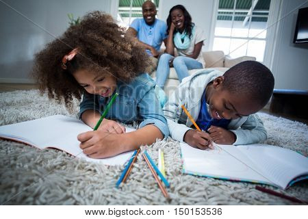 Children doing their homework with parents in background at home
