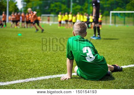 Young caucasian soccer player sitting on grass. Youth football background