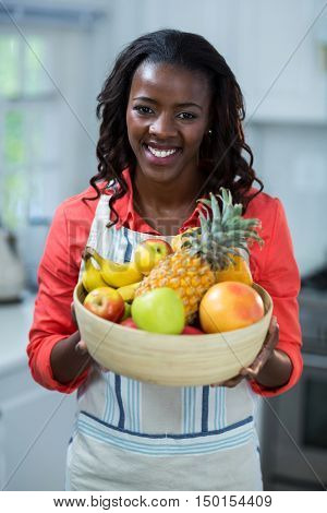 Portrait of woman holding bowl of fruits in kitchen
