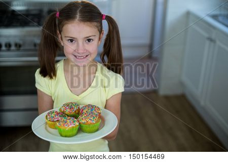 Girl holding a plate of cupcakes at home