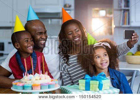 Family taking selfie with birthday cake at home