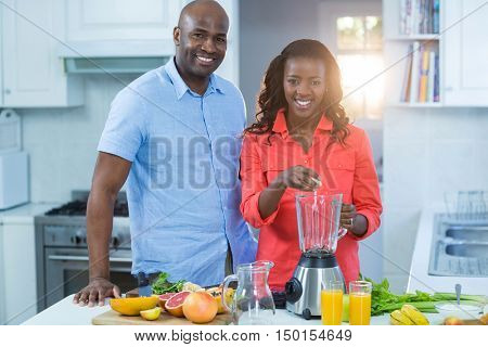 Couple standing with mixer in kitchen