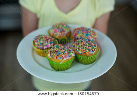Mid-section of girl holding a plate of cupcakes at home