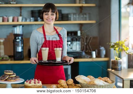 Portrait of waitress holding cup of cold coffee in caf\x92\xA9