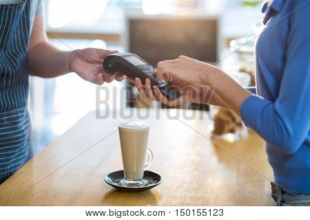 Mid-section of customer making payment through payment terminal at counter in caf\x92\xA9