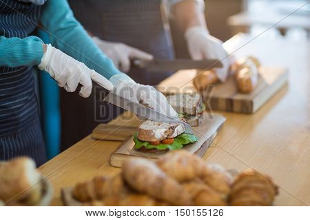 Mid-section of waiter chopping bread roll and sandwich on chopping board in caf\x92\xA9