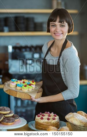Portrait of smiling waitress holding cup cake on tray in caf\x92\xA9