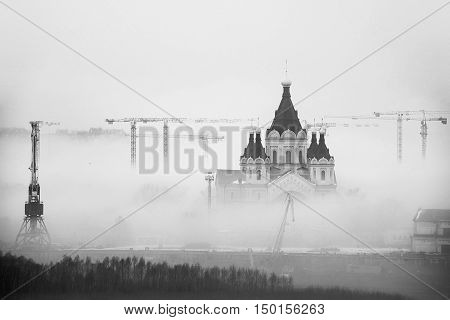 Cathedral of St. Alexander Nevskiy in Nizhny Novgorod Russia covered with fog. Numerous construction cranes. Black and white