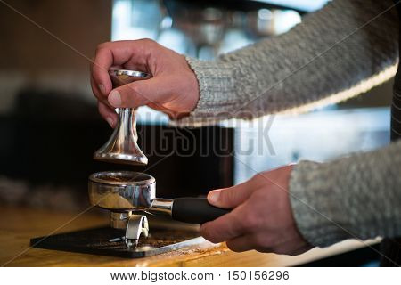 Waiter using a tamper to press ground coffee into a portafilter in caf\x92\xA9