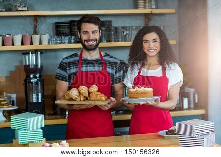 Portrait of waiter and waitress holding a tray of croissants and cake in caf\x92\xA9