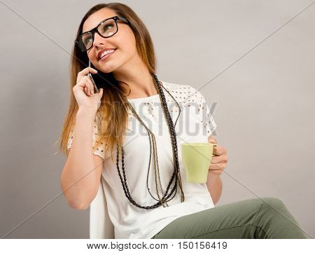 Beautiful woman talking at phone while drinking a coffee