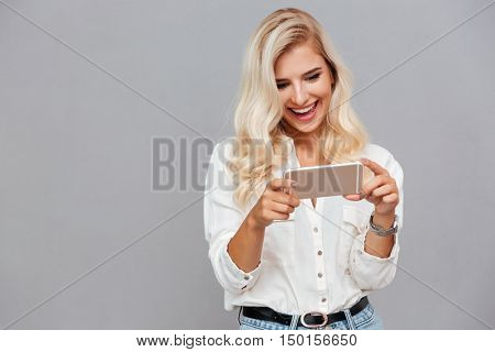 Cheerful young woman using mobile phone isolated on a gray background