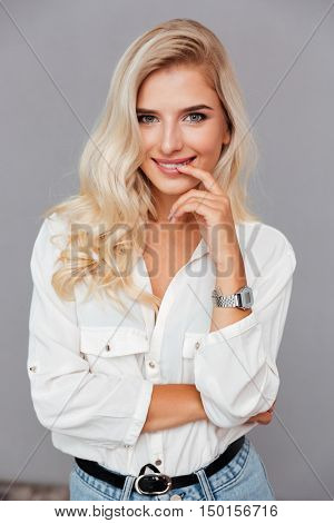 Close up portrait of beautiful wondered woman looking at camera isolated on a gray background