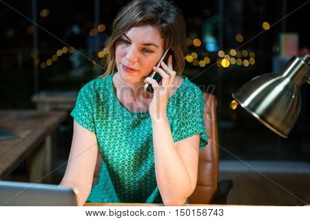 Businesswoman talking on mobile phone while working on laptop in the office