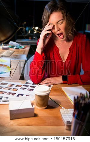 Stressed businesswoman yawning at her desk in the office