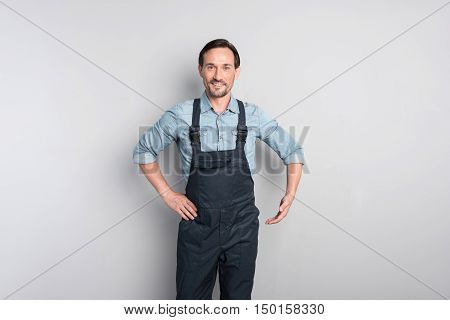 Optimistic person. Happy optimistic good looking man moving his hand and smiling while looking at you