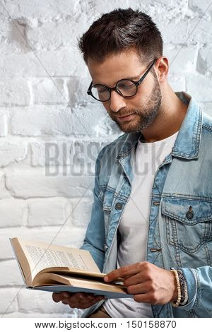 Young goodlooking caucasian man in glasses sitting at white brick wall, reading book.
