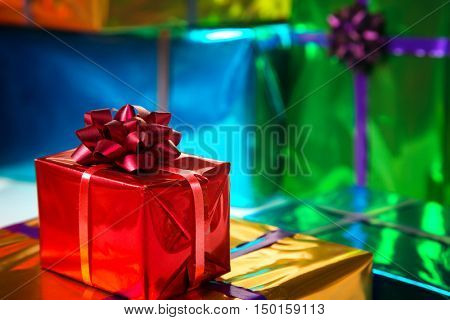 colorful and shiny gift boxes . Focus on red bow.