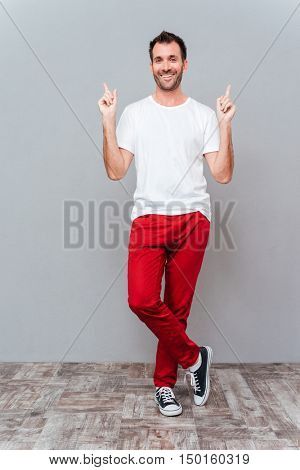 Full length portrait of a smiling casual man pointing two fingers up over grey background