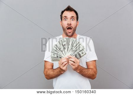 Happy casual man holding bills of US dollars over gray background