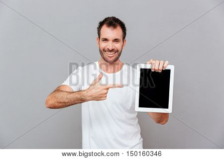 Portrait of a handsome man pointing finger on blank tablet computer screen isolated on a gray background