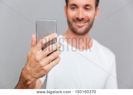 Portrait of a smiling man making selfie photo over gray background