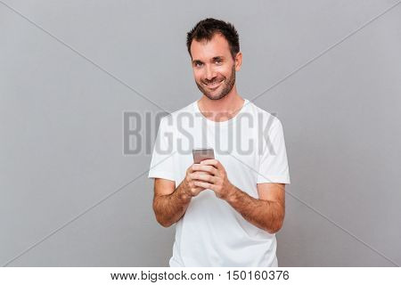Happy uoung man holding smartphone and looking at camera over grey background