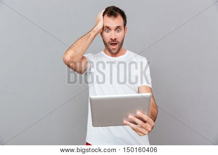 Surprised young man in white tshirt holding tablet over grey background