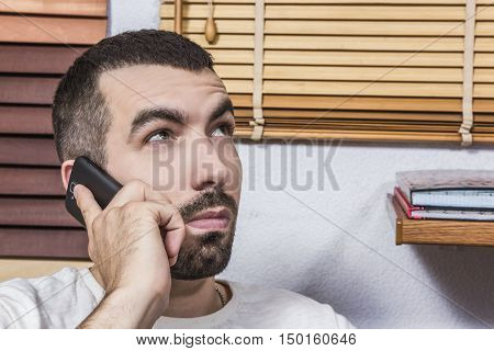 Man talking on the phone on the background of blinds