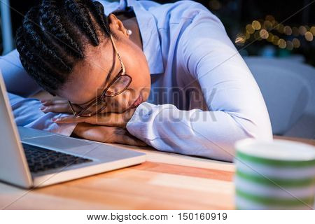 Tired businesswoman sleeping on the desk in the office