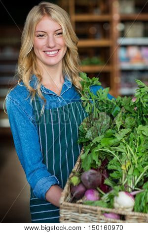 Portrait of smiling staff holding a basket of fresh vegetables in organic section of supermarket