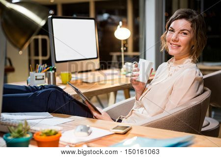 Portrait of businesswoman holding digital tablet and coffee cup at her desk in the office