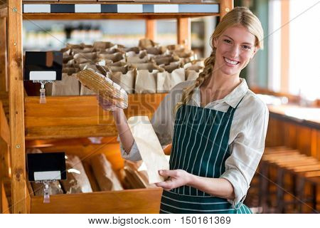 Portrait of smiling female staff packing a bread in paper bag at supermarket