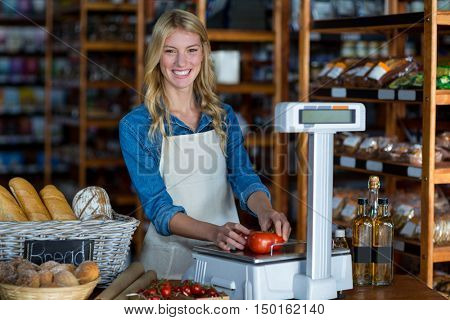 Portrait of smiling female staff weighting vegetables on scale in supermarket
