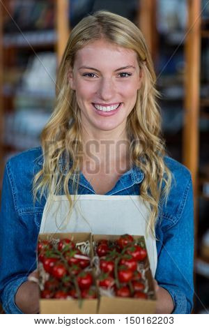 Portrait of smiling female staff holding box of cherry tomato in supermarket
