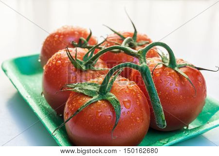 Red tomatoes in a plate near window with natural light
