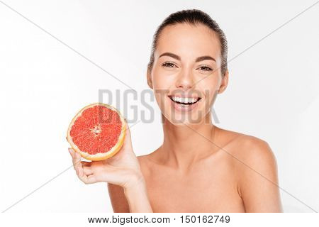 Beauty portrait of a happy woman holding grapefruit isolated on a white background