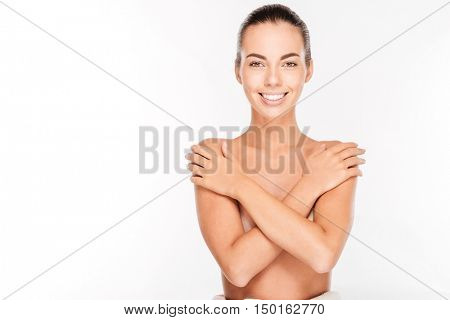 Beautiful young nude woman with arms crossed on her chest isolated on white background