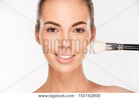 Beautiful young woman apply powder on her face isolated on white background