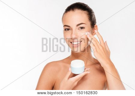 Portrait of young woman applying moisturizer cream on her face isolated on white background